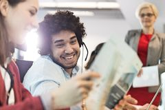 Smiling young businessman wearing headset with colleagues in office Stock Photography