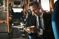 Smiling young businessman listening to music on his morning comm royalty free stock photography