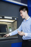 Smiling young businessman withdrawing money from the ATM Royalty Free Stock Photo