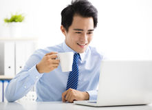 Smiling young businessman working on laptop Stock Image