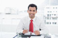Smiling young businessman writing in diary at office. Portrait of a smiling young businessman writing in diary at a bright office Stock Photos