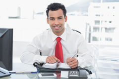 Smiling young businessman writing in diary at office. Portrait of a smiling young businessman writing in diary at a bright office Royalty Free Stock Photography