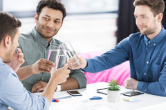 Smiling young businessmen drinking water and discussing new project Stock Photo