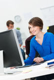 Smiling young businesswoman in a busy office Royalty Free Stock Image