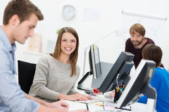 Smiling young businesswoman in a busy office. Sitting at her desk at her computer surrounded by hardworking colleagues Stock Photo