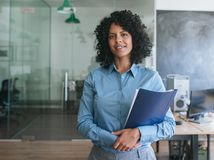 Smiling young businesswoman carrying paperwork while standing in an office stock images