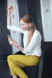 Smiling young businesswoman cheering while holding mobile phone on chair in office Stock Photos