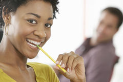 Smiling Young Businesswoman Chewing Pencil Royalty Free Stock Photo