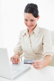 Smiling young businesswoman doing online shopping Stock Photo