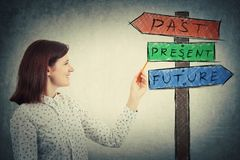 Past present future. Smiling young businesswoman drawing a signpost with arrows that shows past, present and future. Lost in time colorful road sign, destiny Royalty Free Stock Image