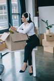 Smiling young businesswoman in headphones using smartphone while unpacking box in new office royalty free stock photo