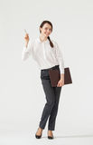 Smiling young businesswoman holding clipboard and indicating som Royalty Free Stock Photo