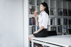 Smiling young businesswoman holding a coffee and sitting on a table, looking away Stock Photo