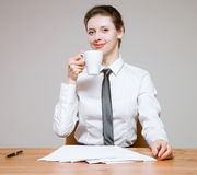Smiling young businesswoman  holding a cup of tea on workplace Royalty Free Stock Photography