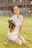 Smiling young businesswoman holding high heels while sitting in office lawn Stock Image