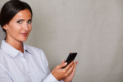 Smiling young businesswoman holding mobile phone Royalty Free Stock Photography