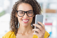 Smiling young businesswoman holding a smartphone Stock Images