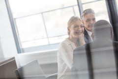 Smiling young businesswoman with male colleagues in meeting room Royalty Free Stock Photos