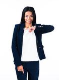 Smiling young businesswoman pointing finger away Royalty Free Stock Images