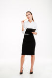 Smiling young businesswoman pointing pencil at blank clipboard Royalty Free Stock Photos