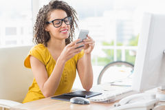 Smiling young businesswoman sending a text Stock Image
