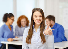 Smiling young businesswoman showing thumbs up Stock Photos