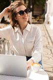 Smiling young businesswoman sitting at the cafe royalty free stock images