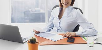 Smiling businesswoman working in the office and checking charts royalty free stock images