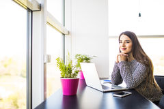 Smiling young businesswoman sitting at office desk and typing on a laptop, she is looking at camera Stock Photo