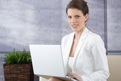 Smiling young businesswoman on sofa with computer Stock Images