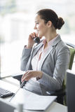 Smiling young businesswoman talking on landline phone in office Stock Photo