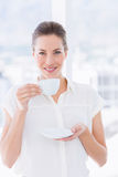 Smiling young businesswoman with tea cup. Portrait of a smiling young businesswoman with tea cup standing in a bright office Royalty Free Stock Photos