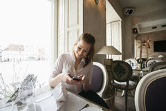Smiling young businesswoman text messaging on cell phone at restaurant table Royalty Free Stock Photography