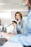 Smiling young businesswoman using landline phone in office stock image