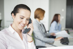 Smiling young businesswoman using landline telephone with colleagues in background at office Royalty Free Stock Photography