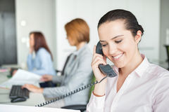 Smiling young businesswoman using landline telephone with colleagues in background at office stock images