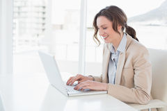 Smiling young businesswoman using laptop in office Royalty Free Stock Image