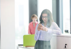 Smiling young businesswoman using mobile phone with male colleague in background at office Stock Image