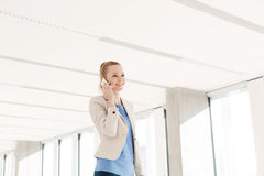Smiling young businesswoman using mobile phone in new office Stock Photography