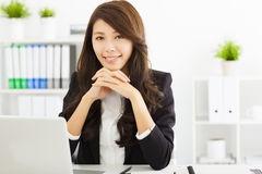 Smiling young businesswoman working in the office Stock Images