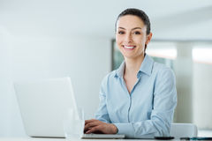 Smiling young businesswoman working at office desk Royalty Free Stock Images
