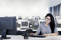 Smiling young businesswoman working in the office stock photos