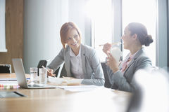 Smiling young businesswomen having lunch at table in office Royalty Free Stock Image