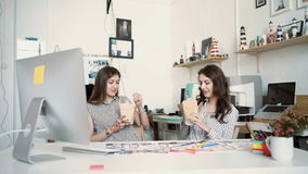 Smiling young businesswomen having lunch at table in office.  stock video footage