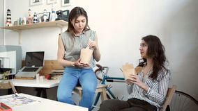 Smiling young businesswomen having lunch at table in office.  stock video