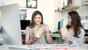 Smiling young businesswomen having lunch at table in office stock footage