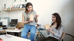 Smiling young businesswomen having lunch at table in office stock video footage
