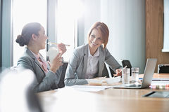 Smiling young businesswomen having lunch at table in office Royalty Free Stock Images