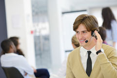 Smiling young call center executive at startup office Stock Photos