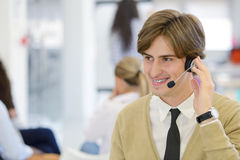 Smiling young call center executive at startup office Stock Photo